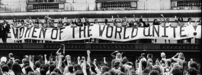 Black and white, vintage photo depicting a crowd of women holding a big banner with text: Women of the world unite!