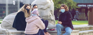 Image of 4 students wearing masks, sitting on the steps next to Queen's Tower